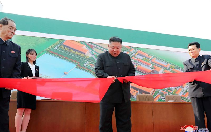 In this photograph provided by the North Korean government, North Korean leader Kim Jong Un, center, cuts a tape during his visit to a fertilizer factory in South Pyongan, near Pyongyang, on May 1, 2020 - KCNA via KNS