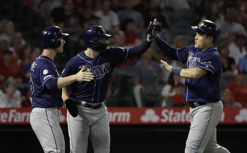From left, Tampa Bay Rays' Joey Wendle, Austin Meadows and Ji-Man Choi meet at home plate after all three were driven in by a bases-loaded double from Travis d'Arnaud during the sixth inning of a baseball game against the Los Angeles Angels, Saturday, Sept. 14, 2019, in Anaheim, Calif. (AP Photo/Marcio Jose Sanchez)