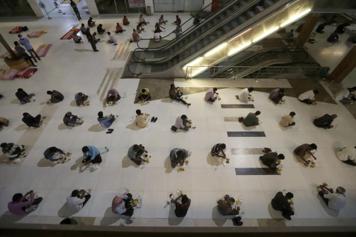 Migrant workers from other states and homeless people eat dinner at a shelter set up in a mall during a lockdown to prevent the spread of new coronavirus in Ahmedabad, India. India, on April 7, 2020. (AP Photo/Ajit Solanki, File)