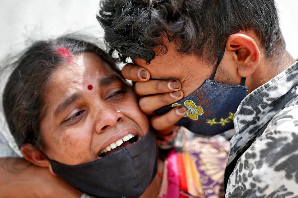 A woman in India mounrs her husband following his death due to CovidREUTERS