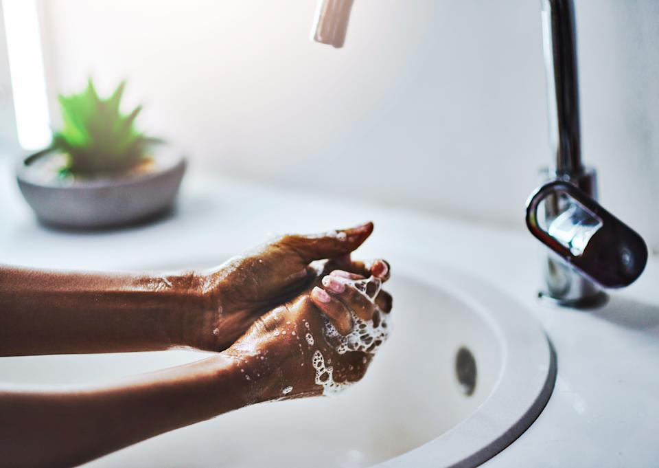 When washing your hands, scrub for at least 20 seconds with warm, soapy water. Don't miss your thumbs, fingertips, and in between fingers. Then dry your hands off. (Photo: Delmaine Donson via Getty Images)