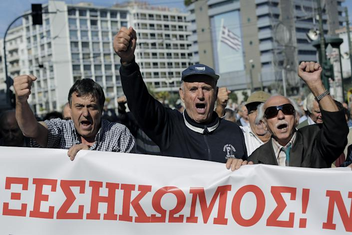 """Pensioners hold a banner which reads in Greek """"Uprising"""" as they chant anti austerity slogans during a protest in central Athens, on Thursday, Oct. 31, 2013. Elderly Greeks have faced successive pension cuts since Greece began relying on international rescue loans in 2010, and have also been hard hit by health care cuts. (AP Photo/Petros Giannakouris)"""