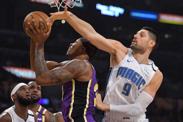 Los Angeles Lakers center Dwight Howard, center, shoots as Orlando Magic center Nikola Vucevic defends during the first half of an NBA basketball game Wednesday, Jan. 15, 2020, in Los Angeles. (AP Photo/Mark J. Terrill)