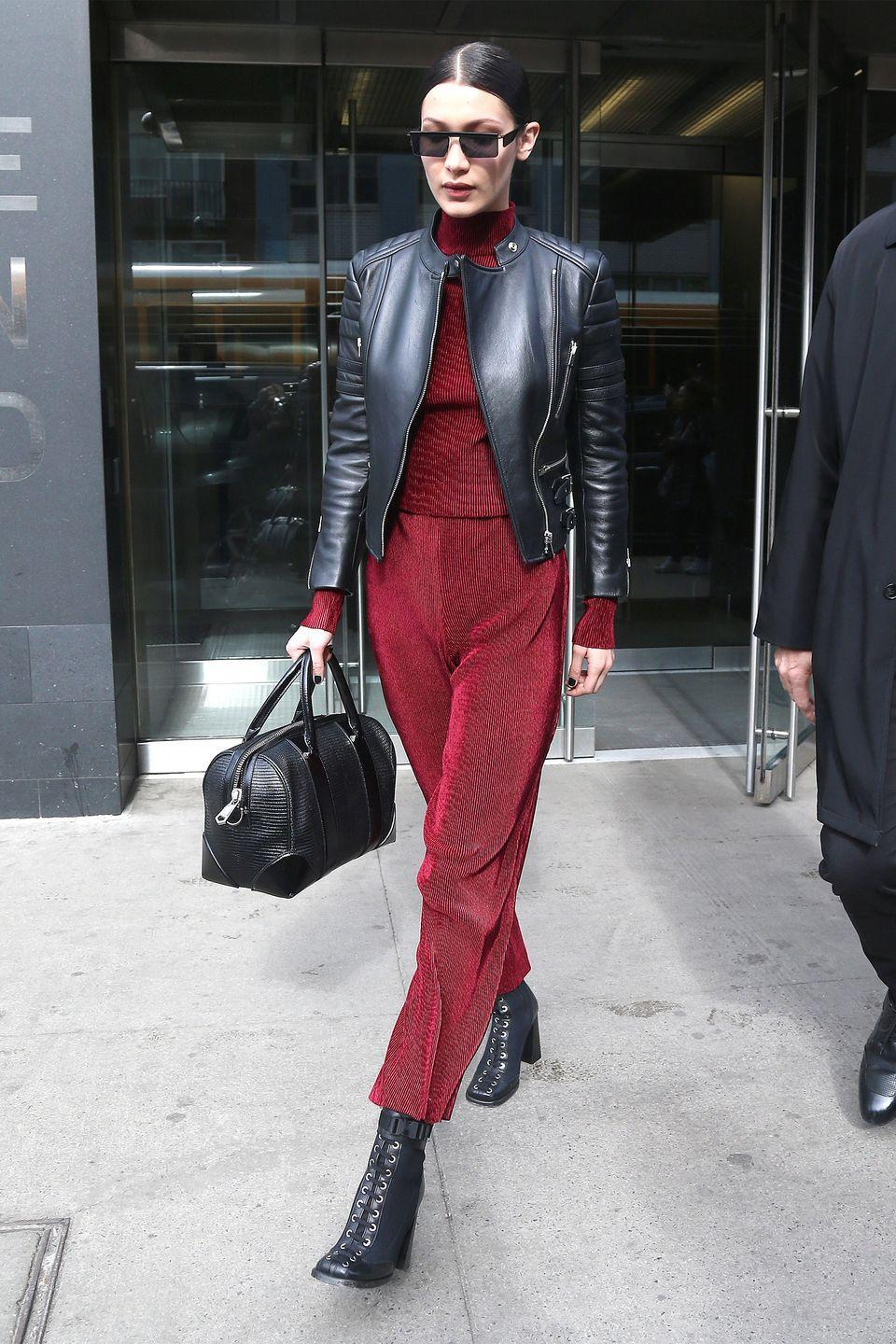 <p>In ribbed burgundy turtleneck and trouser set with a leather moto jacket, Givenchy bag, and lace-up square-toe ankle boots while out in New York City. </p>