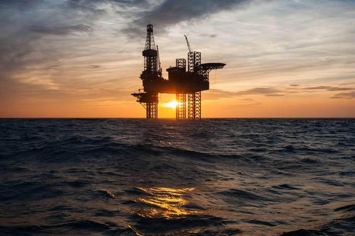 The silhouette of an offshore oil drilling rig at sunset.