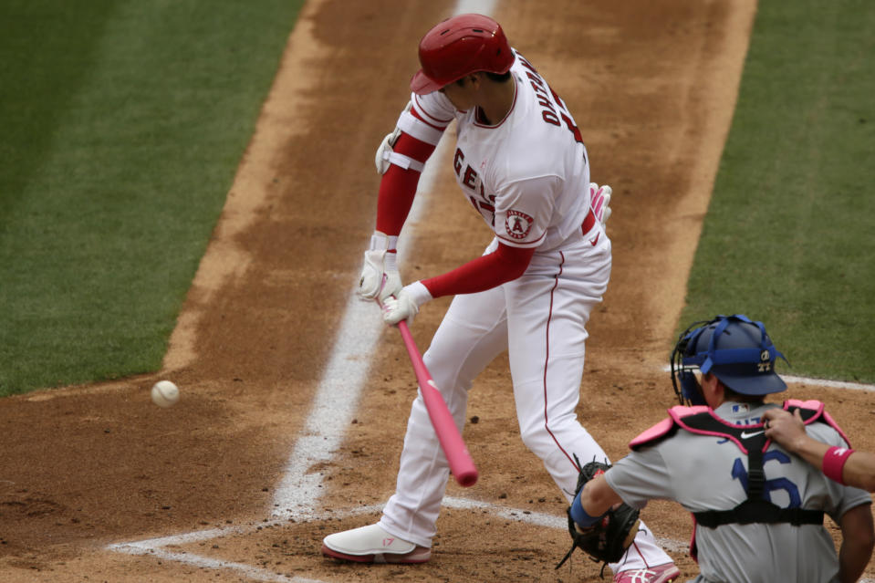 Los Angeles Angels designated hitter Shohei Ohtani, left, hits an infield single with Los Angeles Dodgers catcher Will Smith watching during the first inning of a baseball game in Anaheim, Calif., Sunday, May 9, 2021. (AP Photo/Alex Gallardo)