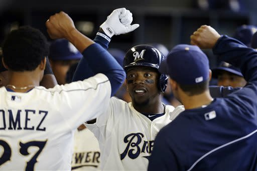 Milwaukee Brewers' Rickie Weeks (23) high-fives teammates in the dugout after his two-run home run against the Chicago White Sox during the first inning of an exhibition baseball game, Saturday, March 30, 2013, in Milwaukee. (AP Photo/Jeffrey Phelps)