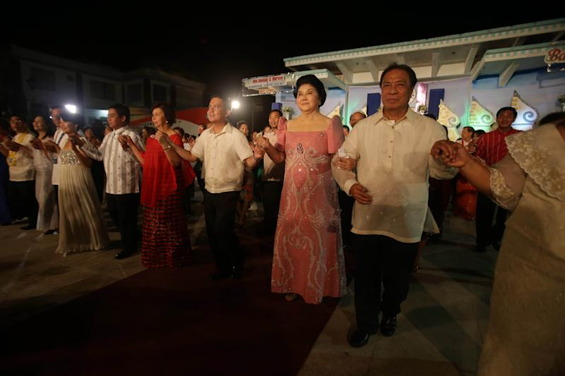 In this May 4, 2013 photo, former Philippine First Lady Imelda Marcos, second from right, dances during a town fiesta in Paoay, Ilocos Norte province, northern Philippines. Twenty-seven years after her dictator husband was ousted by a public revolt, Imelda Marcos has emerged as the Philippines' ultimate political survivor: She was back on the campaign trail this week, dazzling voters with her bouffant hairstyle, oversized jewelry and big talk in a bid to keep her seat in Congress. (AP Photo/Aaron Favila)