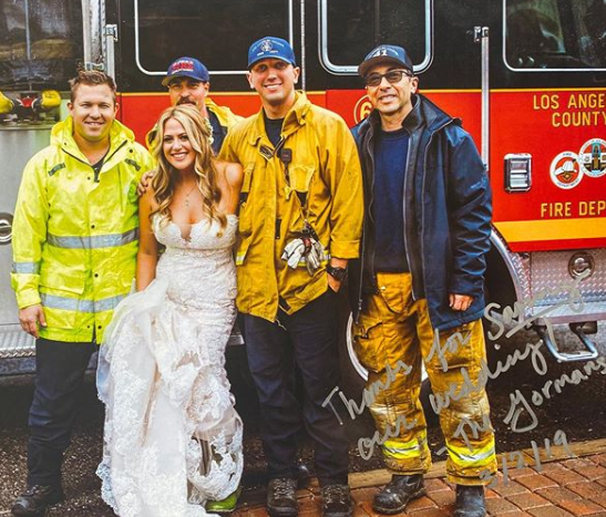 Pictured is the signed photo of the bride posing in her wedding dress with the firemen. Source: Instagram