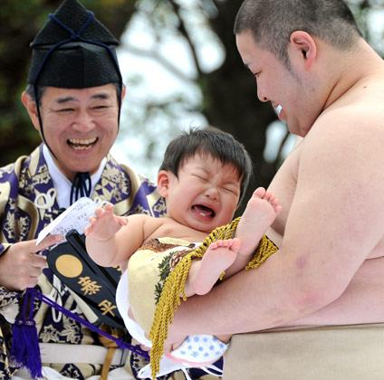 """A student sumo wrestler carrys a crying baby beside a referee (L) clad in a traditional costume during the """"Baby-cry Sumo"""" competition at Sensoji temple in Tokyo on April 21, 2012. Some 100 babies aged under one took part in the annual baby crying contest. Japanese parents believe that sumo wrestlers can help make babies cry out a wish to grow up with good health.    AFP PHOTO/Toru YAMANAKA"""
