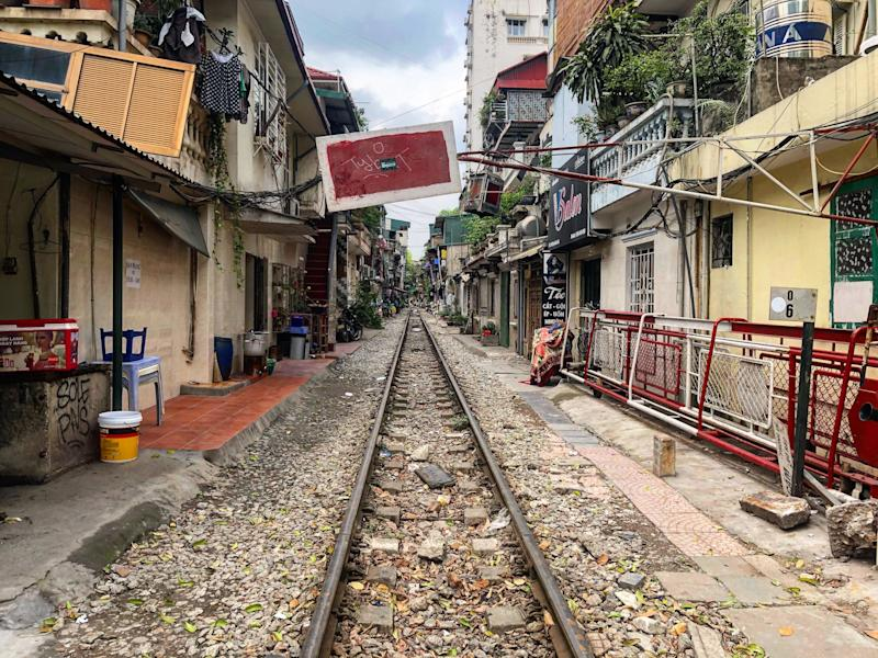 In the crowded streets of smoggy Hanoi, a train passes very, very close by people's homes.