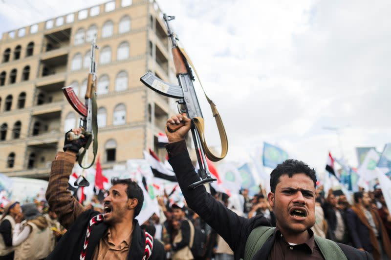 Supporters of Yemen's Houthis hold up their rifles as they rally to celebrate the seventh anniversary of the ousting of the government in Sanaa