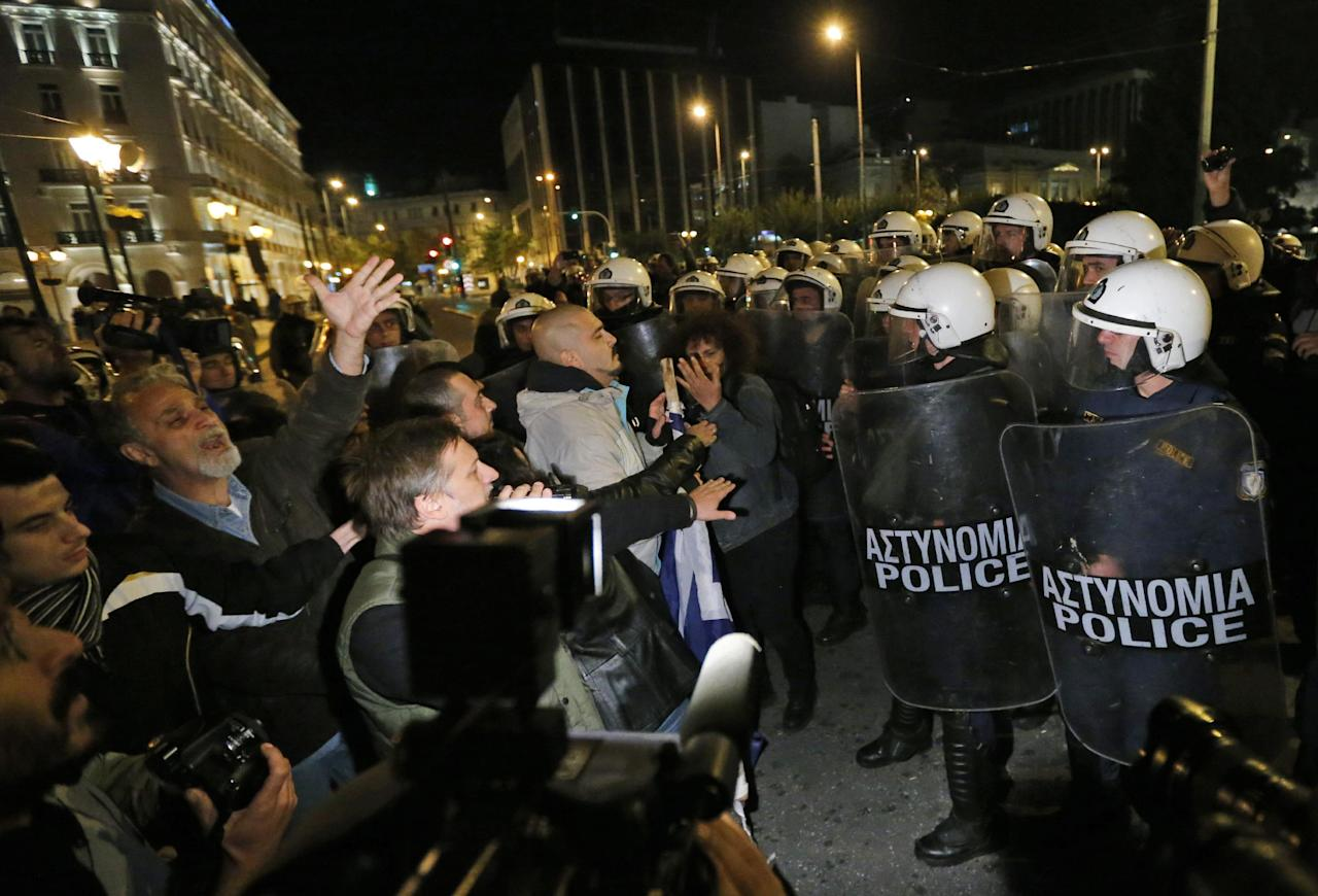 Greek riot police officers, right, push the last remaining protesters off the street, following an anti-austerity rally in front of the Parliament in central Athens, Sunday, Nov. 11, 2012. Thousands of protesters converged on the Greek capital's main square outside the Parliament on Sunday evening, as lawmakers debated the 2013 budget, which includes pension and salary cuts demanded by the country's international creditors in order for them to approve the next vital batch of rescue loans. (AP Photo/Lefteris Pitarakis)