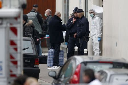 French policemen and police investigators stand in front of the entrance of the Paris offices of Charlie Hebdo, January 7, 2015. REUTERS/Charles Platiau
