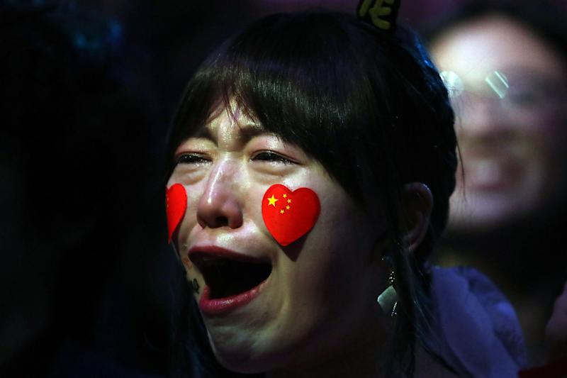 A spectator cries as her favorit China's Ma Long celebrates his winning over Sweden's Mattias Falck on April 28, 2019. Photo: FERENC ISZA/AFP/Getty Images