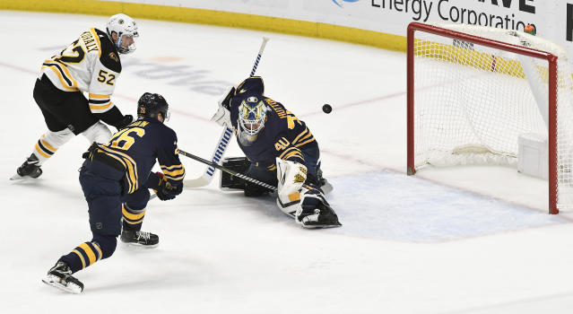 Boston Bruins center Sean Kuraly (52) puts the game-winning goal past Buffalo Sabres goalie Carter Hutton (40) as defenseman Rasmus Dahlin (26) trails the play during overtime of an NHL hockey game in Buffalo, N.Y., Saturday, Dec. 29, 2018. The Boston Bruins beat the Buffalo Sabres 3-2 in overtime. (AP Photo/Adrian Kraus)
