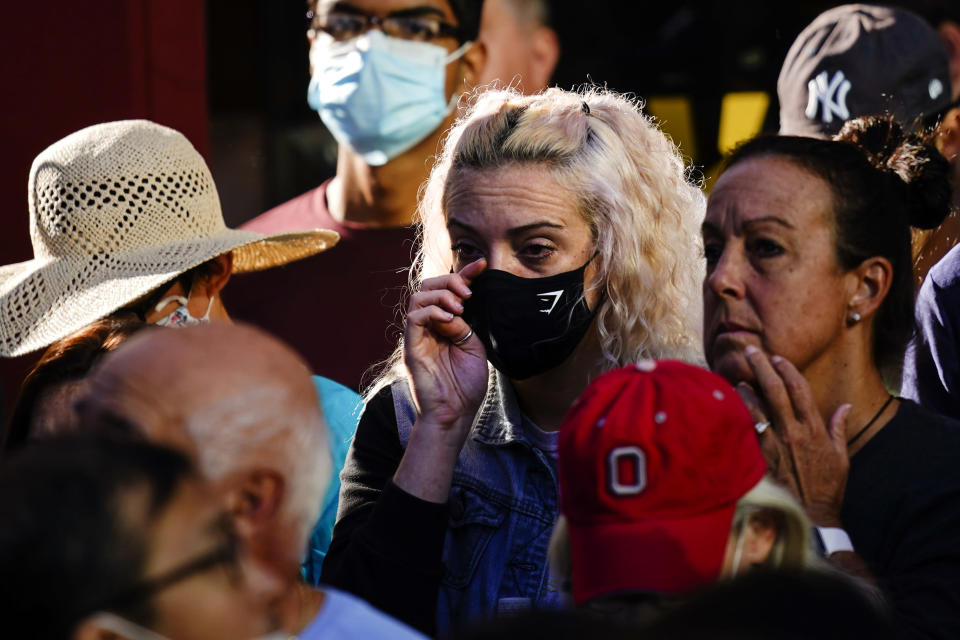 A person wipes her eye as she gathers with others outside the National September 11 Memorial and Museum during a ceremony marking the 20th anniversary of the 9/11 terrorist attacks, Saturday, Sept. 11, 2021, in New York. (AP Photo/Matt Rourke)