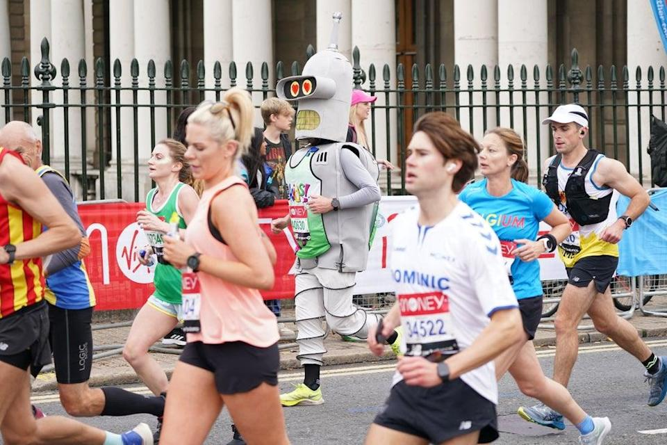 A runner dressed as Bender, the robot from Futurama, passes the Old Naval College (Jonathan Brady/PA) (PA Wire)