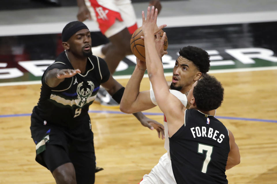 Houston Rockets' Kenyon Martin Jr. drives to the basket between Milwaukee Bucks' Bryn Forbes (7) and Bobby Portis (9) during the first half of an NBA basketball game Friday, May 7, 2021, in Milwaukee. (AP Photo/Aaron Gash)