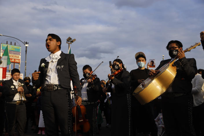 A mariachi band sings in front of the demonstrators as they take part in a peace walk honoring the life of police shooting victim 13-year-old Adam Toledo, Sunday, April 18, 2021, in Chicago's Little Village neighborhood. (AP Photo/Shafkat Anowar)