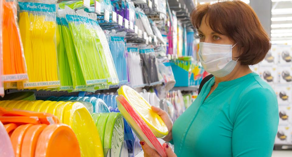 Woman in a supermarket aisle of single-use plastic.