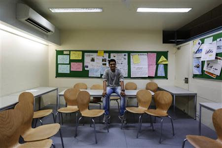 Anuj Trivedi, a 19-year-old student, poses inside his classroom at an institute in Mumbai March 19, 2014. REUTERS/Danish Siddiqui