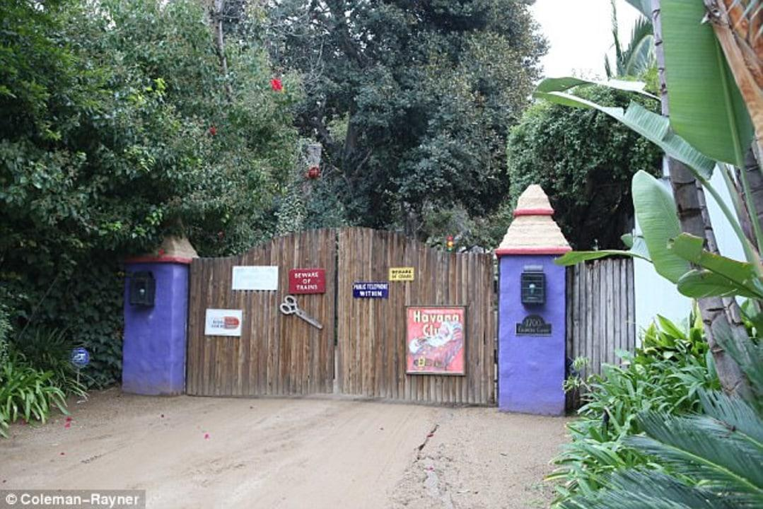 """Before even glimpsing the house itself, visitors get a sense of Fisher's whimsical aesthetic at the entry gate. Featuring lavender paint and signs that read """"BEWARE OF TRAINS,"""" """"PUBLIC TELEPHONE WITHIN"""" and """"BEWARE OF CRABS,"""" in addition to an oversize pair of scissors and a Havana Club poster, this is clearly no ordinary residence."""