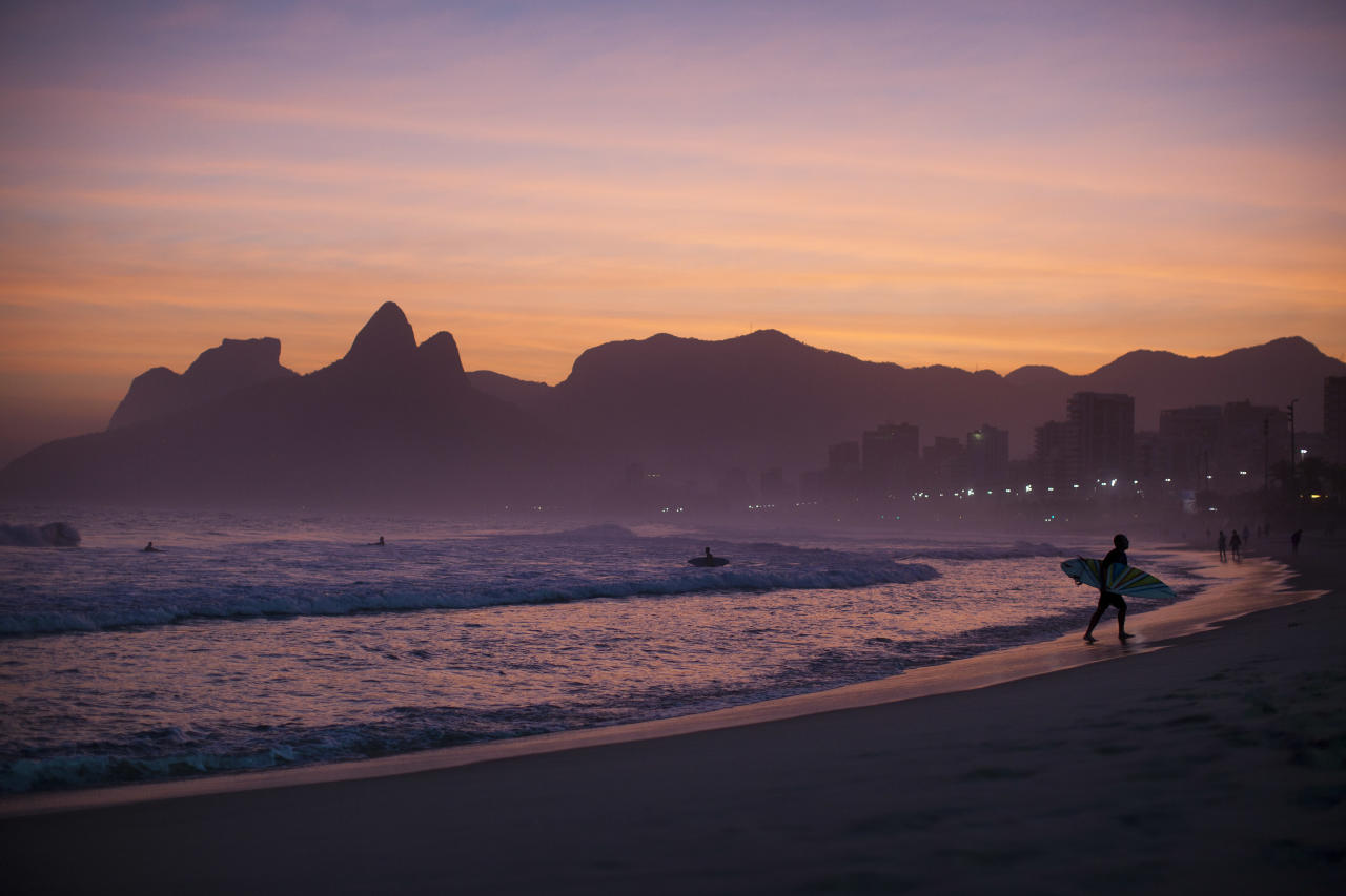 """In this Aug. 25, 2011 photo, a surfer leaves the water as the sun sets at Ipanema beach in Rio de Janeiro, Brazil. The bossa nova song, """"The Girl From Ipanema"""" is turning 50, and to its legions of fans, the decades have only heightened its allure. The tune inspired by a young woman who passed the songwriters in a beach side bar on her way to the waters of Ipanema beach, carries within its chords and lyrics an image of a city that's light and easy, palm trees and blue sky, a sun-kissed life without care. (AP Photo/Felipe Dana)"""