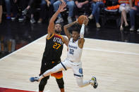 Utah Jazz center Rudy Gobert (27) guards Memphis Grizzlies guard Ja Morant (12) during the second half of Game 5 of an NBA basketball first-round playoff series Wednesday, June 2, 2021, in Salt Lake City. (AP Photo/Rick Bowmer)
