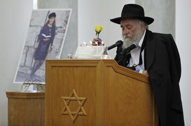 FILE - In this April 29, 2019 file photo, Yisroel Goldstein, Rabbi of Chabad of Poway, holds a yellow rose as he speaks at the funeral for Lori Kaye, who is pictured at left, in Poway, Calif. Prosecutors say John T. Earnest opened fire during the Passover service at the synagogue on April 27, killing Kaye and injuring three people, including the rabbi. A preliminary hearing for Earnest begins Thursday, Sept. 18, 2019, in state court and is expected to last up to two days. (AP Photo/Gregory Bull, File)