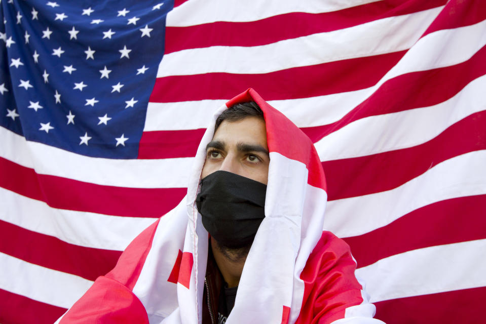 A supporters of the ex-President Mikhail Saakashvili's United National Movement, wearing a face mask to help curb the spread of the coronavirus, sits in front of an American national flag during a rally to protest the election results at the parliament's building in Tbilisi, Georgia, Sunday, Nov. 1, 2020. Preliminary election results show that Georgia's ruling party won the country's highly contested parliamentary election. But the opposition refused to recognize Sunday's results as valid, saying they were manipulated. (AP Photo/Shakh Aivazov)