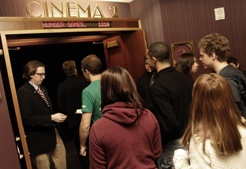"""Movie attendees enter a theater on the opening night of """"The Hunger Games"""" at Regal Cinemas in Los Angeles, March 22, 2012."""