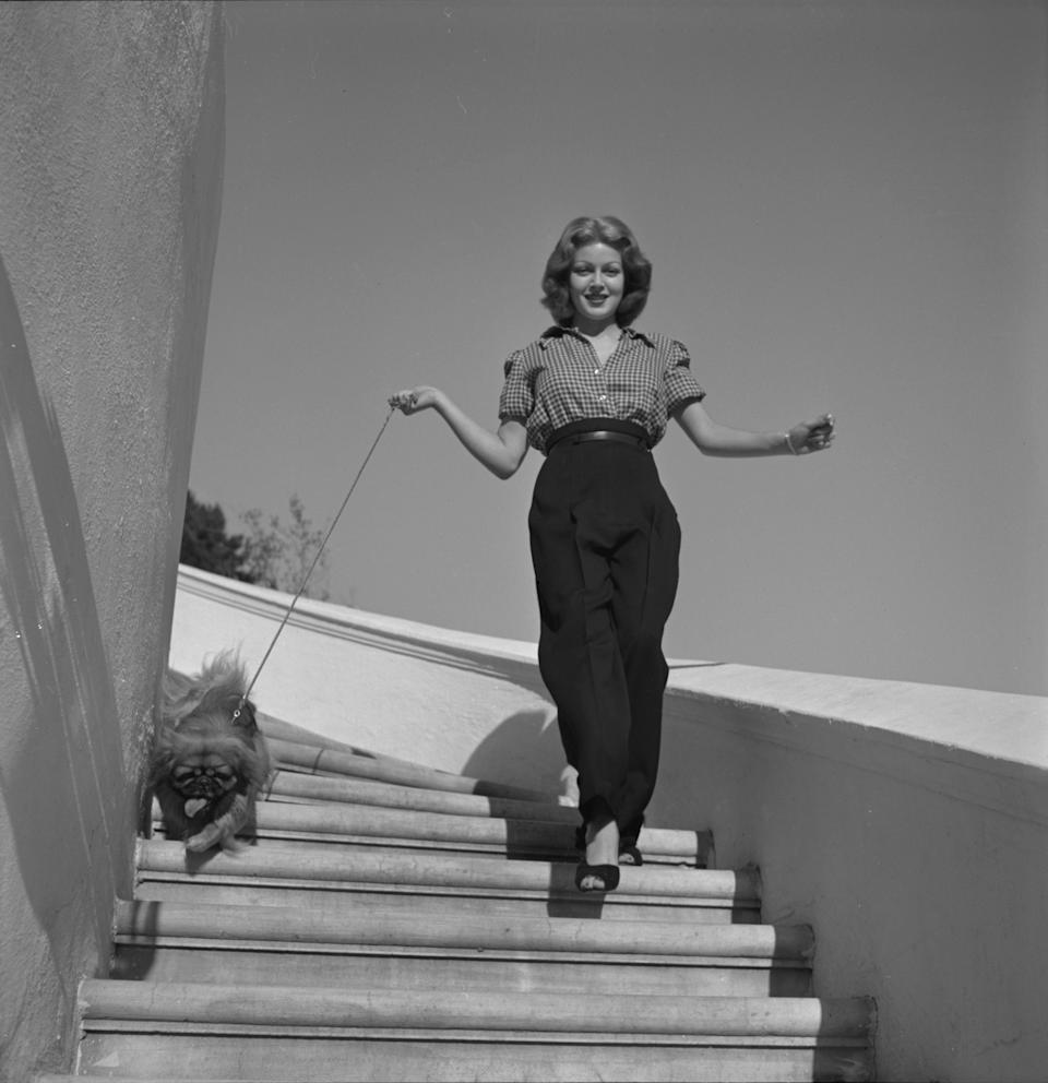 Lana Turner walks down a staircase with her Pekingese dog in Hollywood, California, 1940.