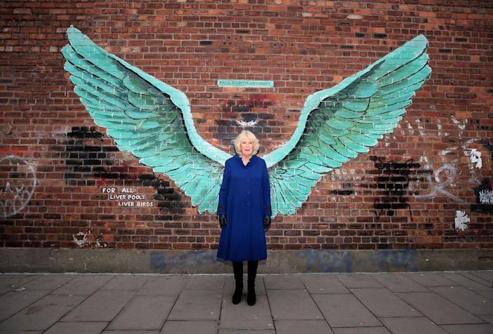 <p>The Duchess posed in front of a mural in Liverpool wearing a royal blue coat and black knee high boots. </p>