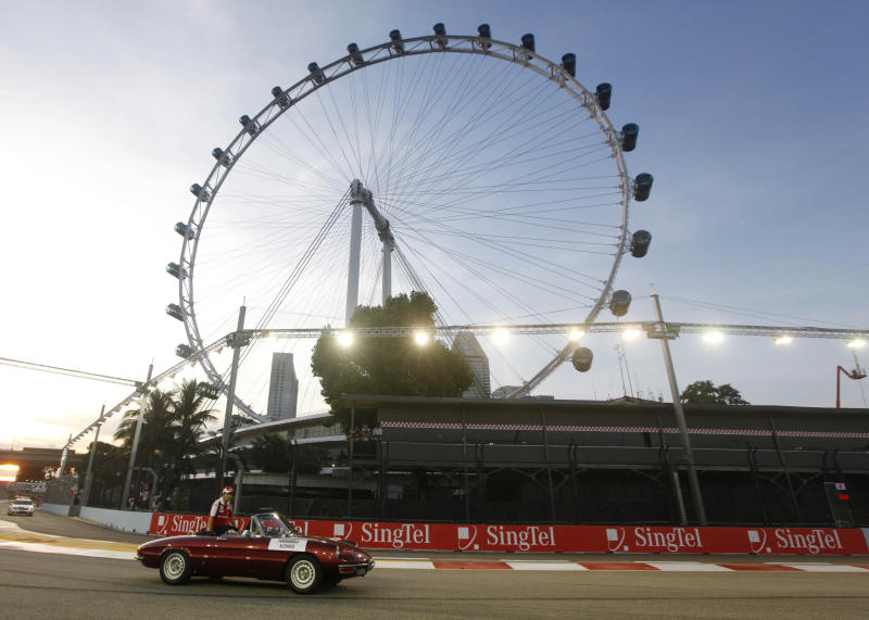 """FILE - In this Sept. 26, 2010 file photo, Ferrari Formula One driver Fernando Alonso of Spain is driven past the 541 foot tall """"Singapore Flyer"""" Ferris wheel during the driver' parade prior to the start of the Singapore Grand Prix on the Marina Bay City Circuit in Singapore. The proposed New York Wheel in the Staten Island borough of New York is planned to be 625 feet tall, and expected to open by the end of 2015. (AP Photo/Mark Baker, File)"""