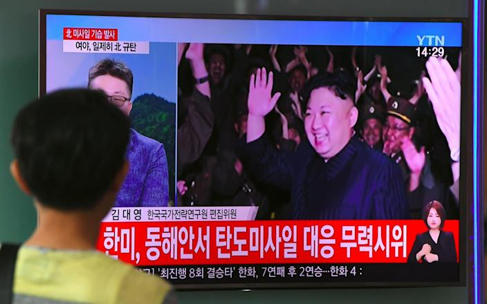 A man watches a television screen showing a video footage of North Korean leader Kim Jong-Un - AFP