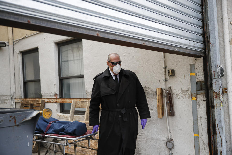 FILE - In this April 3, 2020, file photo, funeral director Tom Cheeseman collects a body from a nursing home in the Brooklyn borough of New York. As the coronavirus takes a devastating toll on seniors in nursing homes, many attorneys are turning down grieving families seeking to sue long-term care providers for wrongful death. (AP Photo/John Minchillo, File)