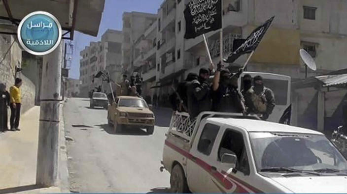 FILE - In this file photo posted on the Twitter page of Syria's al-Qaida-linked Nusra Front on April 25, 2015, which is consistent with AP reporting, shows Nusra Front fighters stand on their vehicles and wave their group's flags as they tour the streets of Jisr al-Shughour, Idlib province, Syria. Turkey and Russia appear to have succeeded in creating a demilitarized zone along the frontlines of Syria's flashpoint Idlib region, after rebels and an al-Qaida-linked alliance pulled back their heavy weaponry in accordance with the agreement. (Al-Nusra Front Twitter page via AP, File)