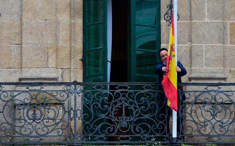 An employee sets the Spanish flag at half mast on a balcony of the council of Betanzos - Credit: MIGUEL RIOPA/AFP
