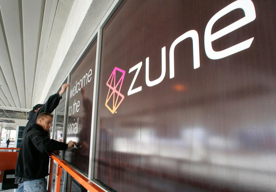 Convention workers put up an advertisement for Zune, Microsoft's portable multimedia player, outside the Las Vegas Convention Center as they prepare for the 2007 International Consumer Electronics Show (CES) in Las Vegas, Nevada January 5, 2007. This year's show runs from January 8-11 and is expected to draw over 150,000 attendees.   REUTERS/Steve Marcus   (UNITED STATES)