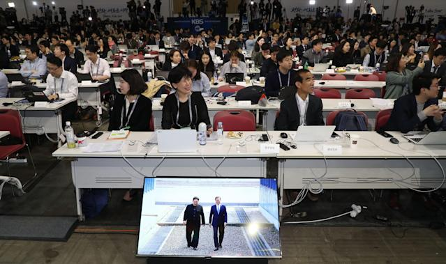 <p>Journalists working within the main press center watch a live-aired historic scene of South Korean President Moon Jae-in (R) and North Korean leader Kim Jong-un crossing the inter-Korean border into the southern side of Panmunjom for historic talks after they briefly entered the northern side of the truce village at the latter's request; in Goyang, northwest of Seoul, South Korea, April 27, 2018. (Photo: Yonhap) </p>