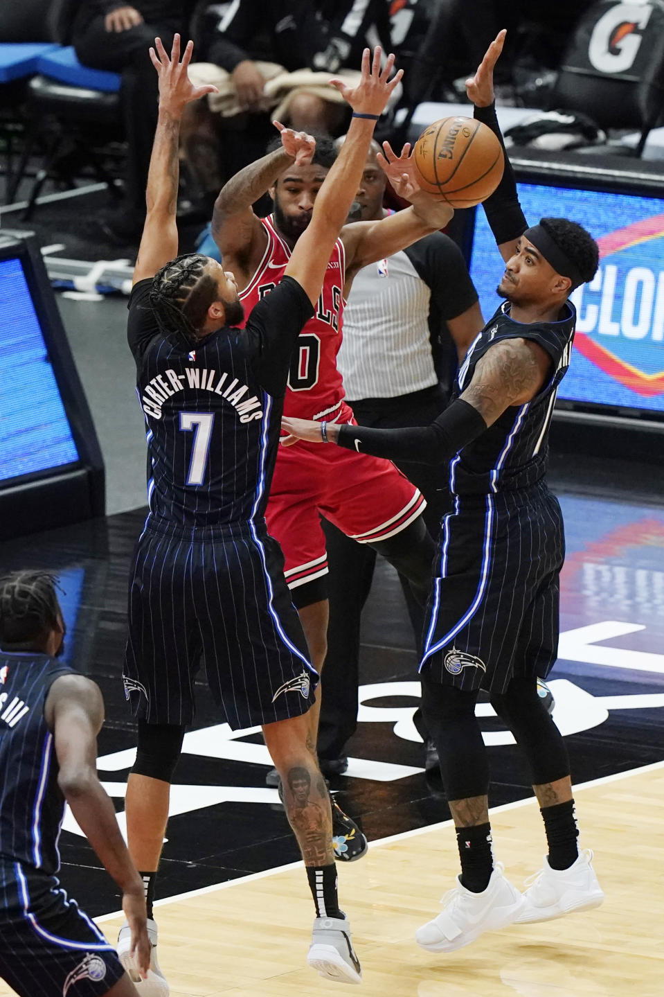 Chicago Bulls guard Coby White, center, passes the ball against Orlando Magic guard Michael Carter-Williams, left, and guard Gary Harris during the first half of an NBA basketball game in Chicago, Wednesday, April 14, 2021. (AP Photo/Nam Y. Huh)