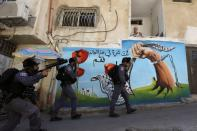 Israeli security force members walk past a house during clashes with Palestinians which erupted over Israel's demolition of a shop in the Palestinian neighbourhood of Silwan in East Jerusalem
