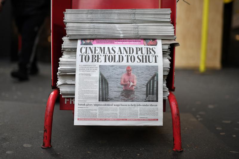 The front page of the Evening Standard newspaper, leading with the story that UK cinemas and pubs are likely to be ordered close later today, is pictured in London on March 20, 2020, during the ongoing coronavirus pandemic. - Britain's Prime Minister Boris Johnson on Thursday said he was confident the country can slow the spread of coronavirus in the next three months through tough measures to cut social contact. The government earlier this week called for more people to work from home, and avoid public transport, pubs, clubs and restaurants, to try to slow infection rates. (Photo by DANIEL LEAL-OLIVAS / AFP) (Photo by DANIEL LEAL-OLIVAS/AFP via Getty Images)
