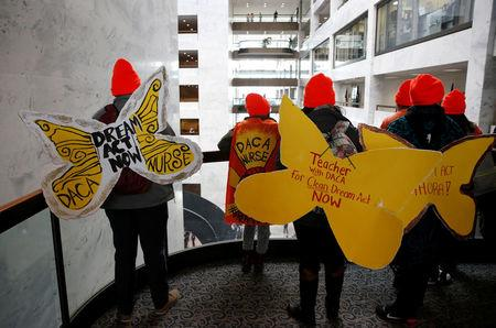Protesters calling for an immigration bill addressing the so-called Dreamers, young adults who were brought to the United States as children, walk through the Hart Office Building on Capitol Hill in Washington, U.S., January 16, 2018. REUTERS/Joshua Roberts