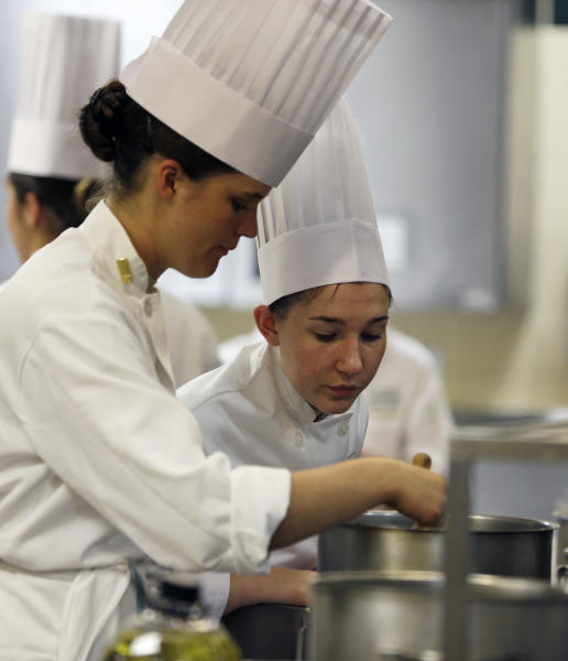 West Point Cadet Erin Mauldin of Albuquerque, N.M., left, and Culinary Institute of America student Clare Wagner of Detroit, work in a kitchen during an exchange program at the culinary school on Wednesday, Oct. 16, 2013, in Hyde Park, N.Y. (AP Photo/Mike Groll)