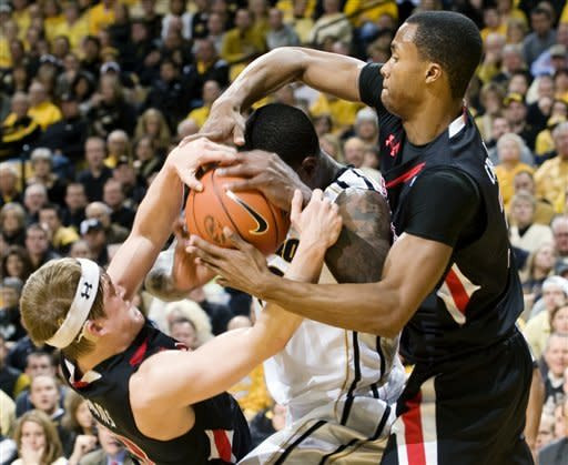 Missouri's Ricardo Ratliffe, center, tries to hold on to the ball as Texas Tech's Luke Adams, left, and Jaye Crockett, right, work to wrestle it away during the second half of an NCAA college basketball game, Saturday, Jan. 28, 2012, in Columbia, Mo. Missouri won 63-50. (AP Photo/L.G. Patterson)