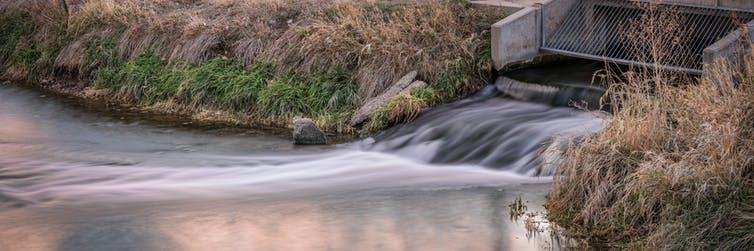 Water flowing out of a concrete grate into a river.