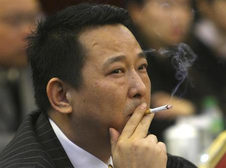 Liu Han, former chairman of Hanlong Mining, smokes a cigarette during a conference in Mianyang