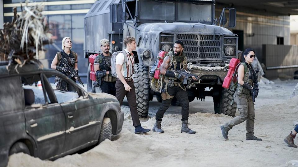 A heist team walks across sand holding weapons surrounded by abandoned cars in a still from Army of the Dead.